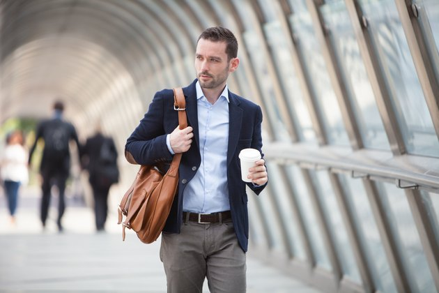 Young attractive man with stomach ulcer drinking coffee on his way