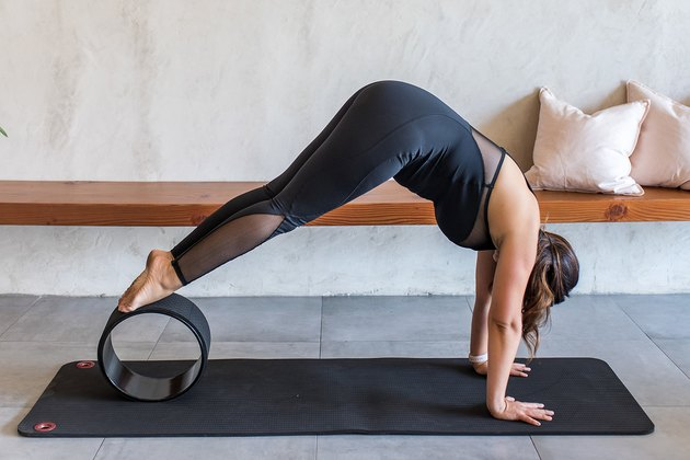 woman doing Pike Press to Handstand Variation (Adho Mukha Vrksasana) with a yoga wheel