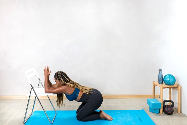 woman doing a kneeling lat stretch