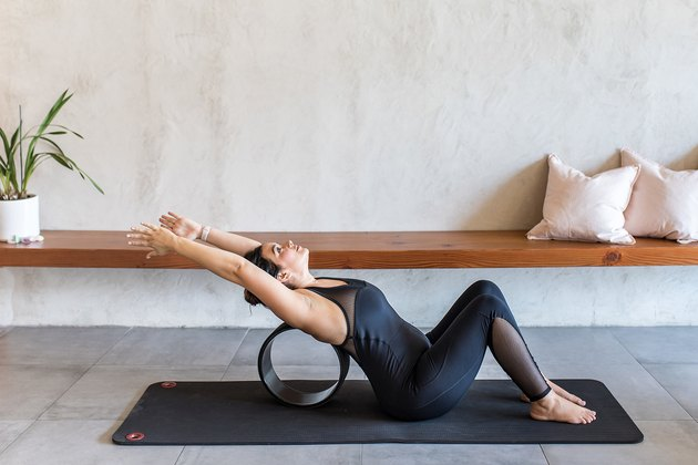 woman doing Spine Release with a yoga wheel