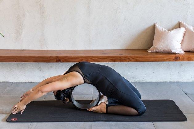 woman doing Pigeon Pose (Kapotasana) with a yoga wheel