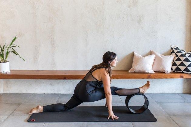 woman doing Half Splits Pose (Ardha Hanumanasana) with a yoga wheel