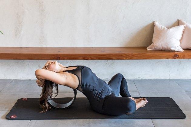woman doing Reclined Easy Sitting Pose (Supta Sukhasana) with a yoga wheel