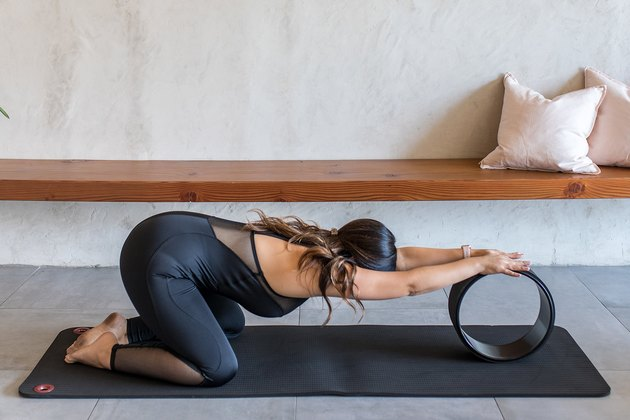 woman doing Child's Pose (Balasana) with a yoga wheel