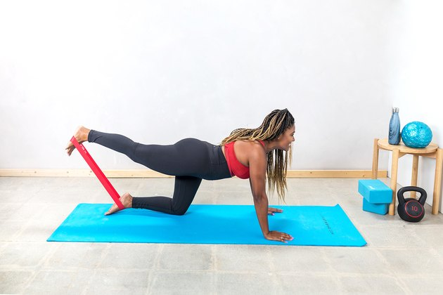 woman doing Glute Kickbacks with a booty band on a yoga mat