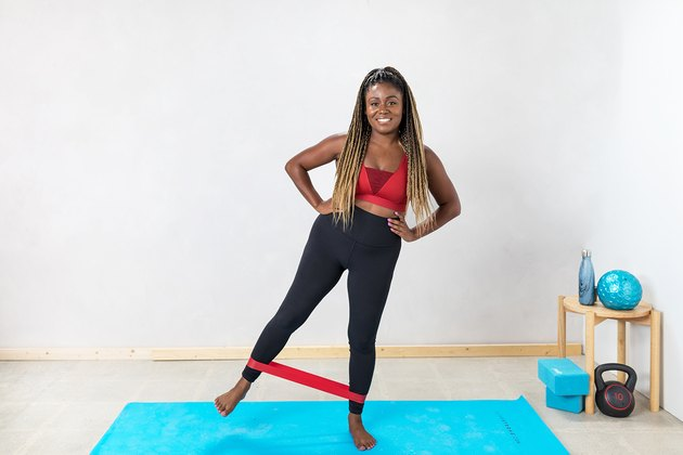 woman doing Side Kicks with a booty band on a yoga mat