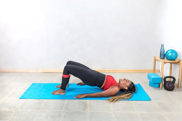 woman doing Glute Bridges with a booty band on a yoga mat