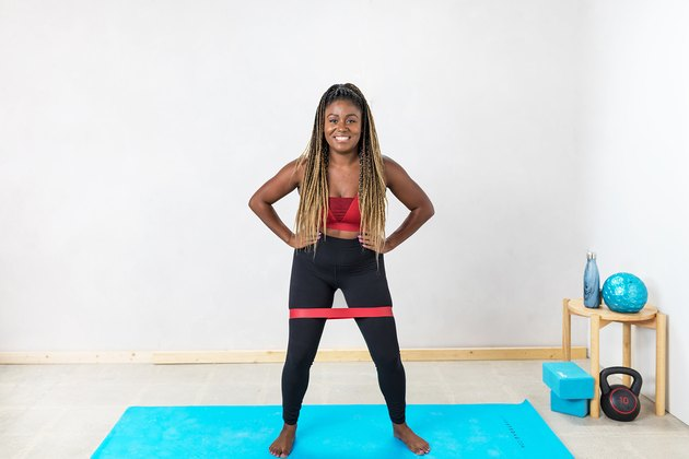 woman doing Lateral Band Walks with a booty band on a yoga mat