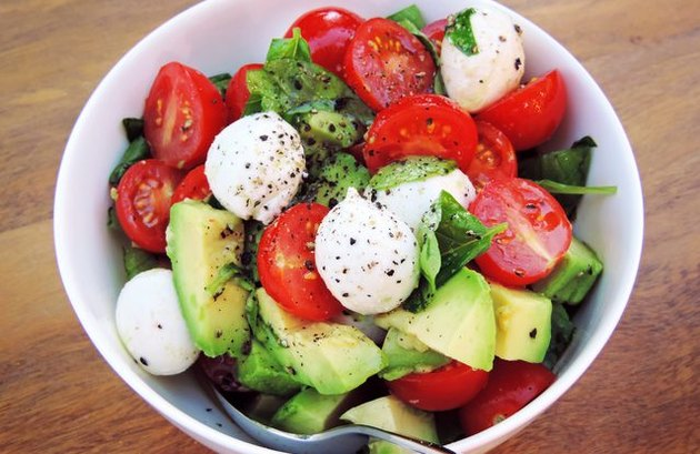 A bowl of chopped avocado and tomatoes, mozzarella balls and chimichurri sauce