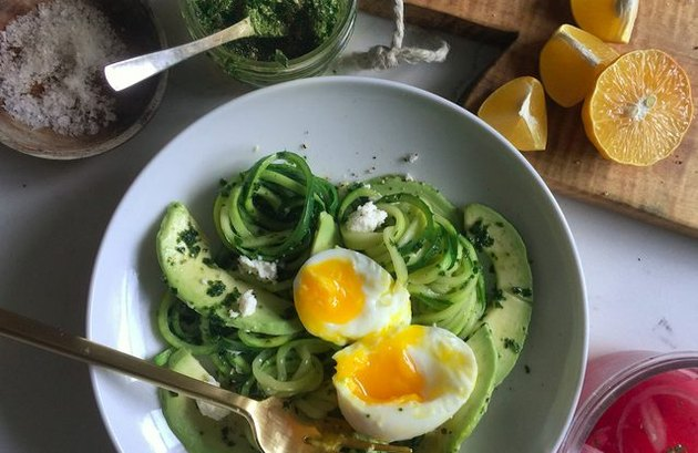 A bowl of zoodles and avocado with pesto, topped with a soft-boiled egg