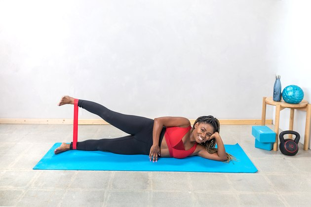 woman doing Lying Side Leg Lifts with a booty band on a yoga mat
