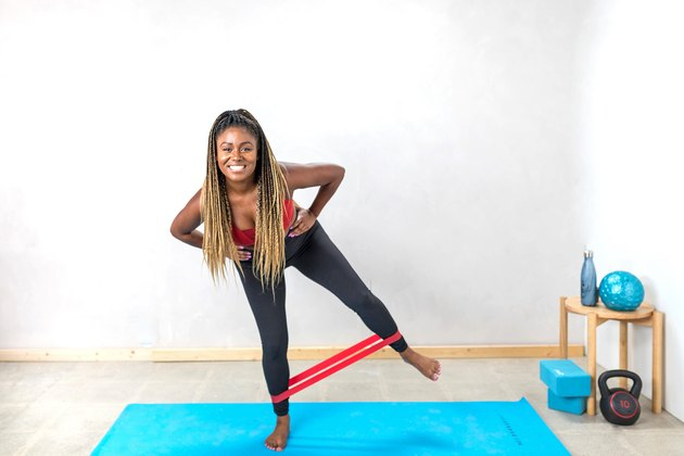 woman doing Side Squat Abductions with a booty band on a yoga mat