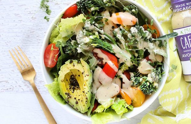 A big salad with greens, avocado, tomatoes, cheese and dressing