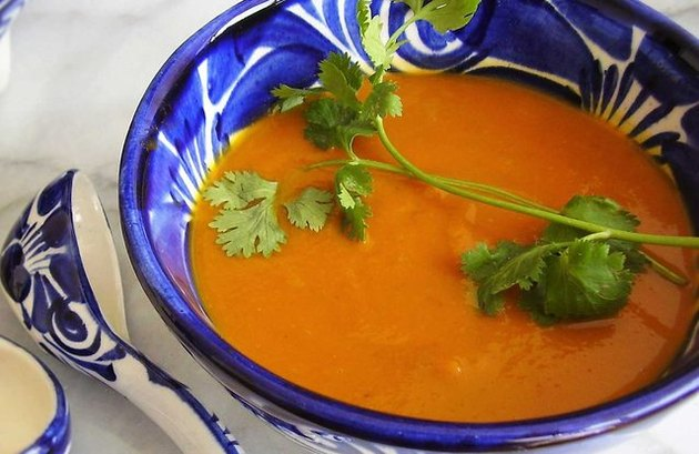 A ceramic bowl decorated with blue and white designs and filled with orange pumpkin soup, topped with parsley