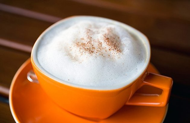 A pumpkin spice latte served in an orange mug, with milk foam and pumpkin pie spice on top