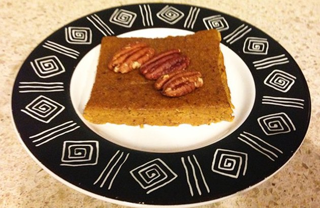 A slice of pumpkin pie, without the crust, on a plate with a black-and-white design