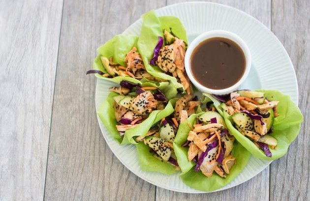 A plate of lettuce cups with kimchi and grilled chicken, and a dipping sauce on the side