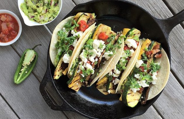 A cast-iron pan with four grilled veggie tacos, and a side of guacamole and salsa