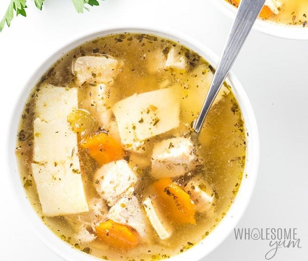 Bowl of chicken and dumplings with carrots.