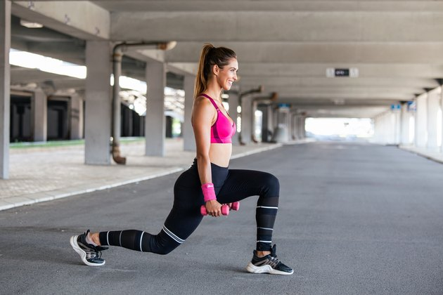 Sporty woman exercising with dumbbells. Photo of active woman in sportswear working out. Dynamic movement. Side view. Sport and healthy lifestyle