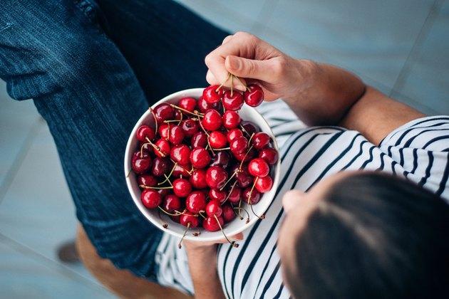 Woman eating cherries as part of an Alkaline Diet