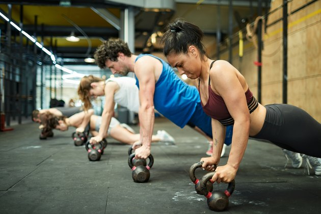Group of hispanic people doing planks with kettlebells at the gym.
