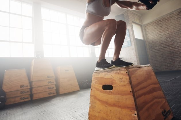 Fit young woman box jumping at a gym gym