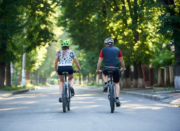Young sporty couple riding bicycles in park.