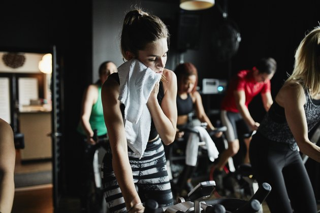 Woman wiping sweat from face with towel while riding indoor bike during cycling class in fitness studio