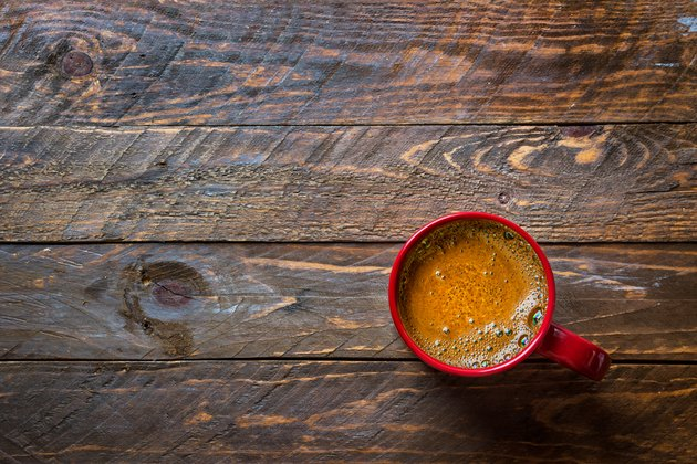 Red mug with freshly brewed coffee with appetizing crema on aged wood kitchen table. Cozy winter fall holiday atmosphere copy space