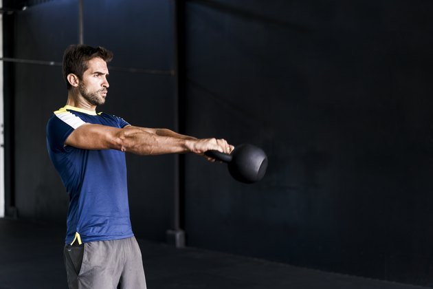 Determined male exercising in gym with kettle bell