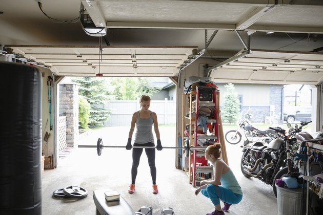 Young women friends working out, weightlifting in garage