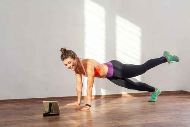 Woman doing a plank with leg lift during an at-home video workout challenge