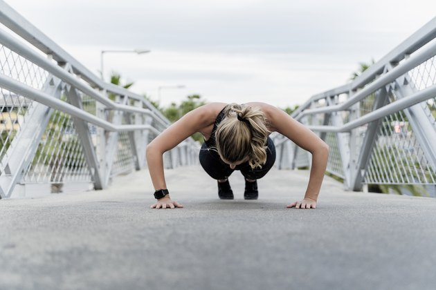 Sporty woman doing push ups, working out on a bridge