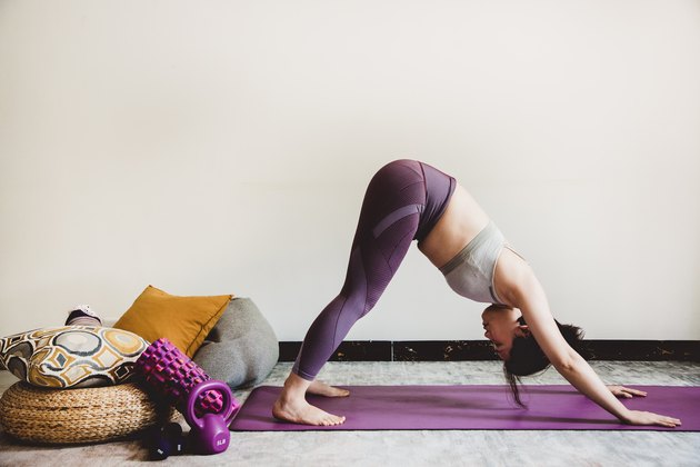 Woman doing pike push-ups during a body-weight shoulder workout at home