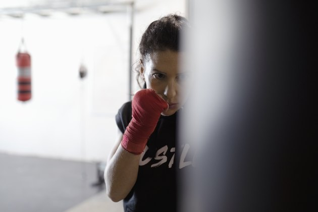 Tough, focused female boxer training at punching bag in gym
