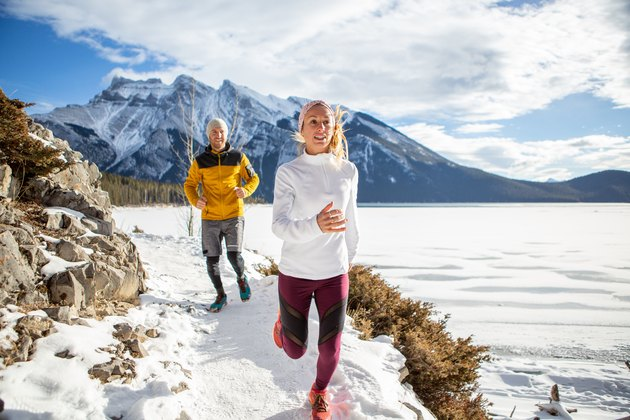 Two people exercising for cross-country running in winter jogging on snowy path