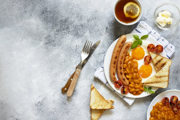 English breakfast with fried sausages, beans, mushrooms, fried eggs, grilled cherry tomatoes. Served with a cup of tea with lemon, bread toast and butter. Gray background, top view, copyspace