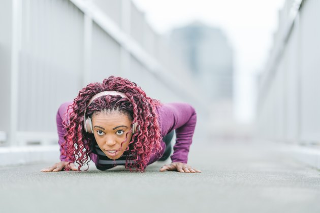 Determined sports woman doing push-ups in city