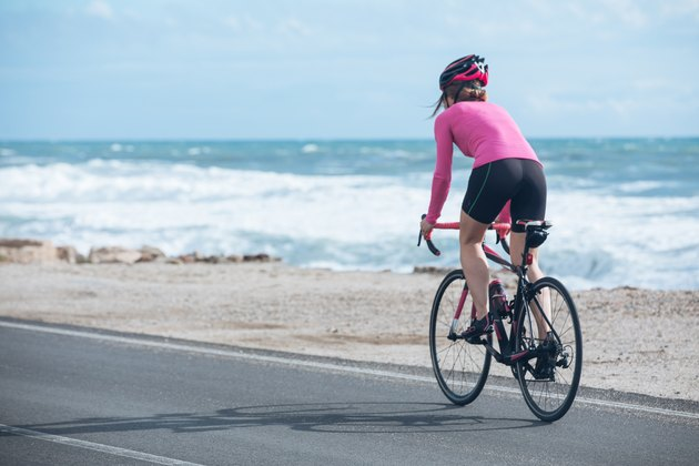 woman cyclist riding a bike on the road close to sea