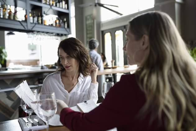 Women friends looking at a menu, dining in restaurant