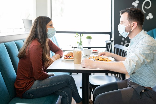 photo of Couple wearing Face Masks eating at a restaurant
