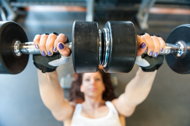 Young woman at gym working her arms with dumbbells