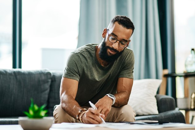 man sitting on a couch writing in a journal