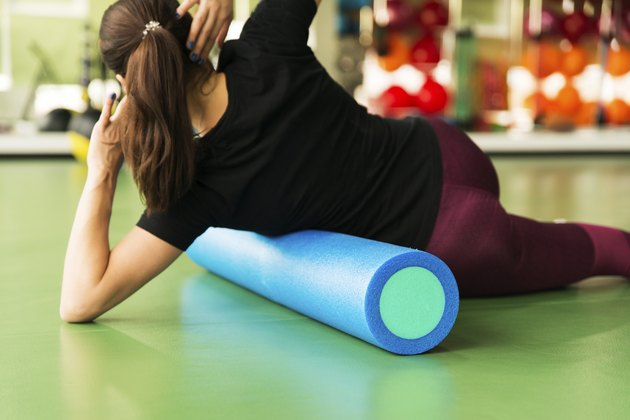 Woman doing foam roller exercise for lats on a floor