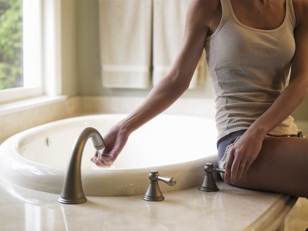 Young woman sitting on edge of bathtub, hand under faucet, mid section