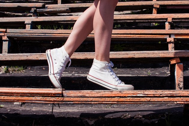 Woman model feet wearing sneakers walking down the bench