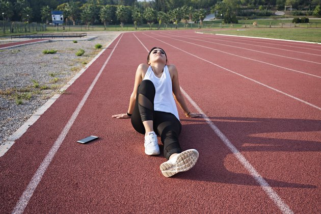 Tired sportswoman lonely sitting in middle of track.
