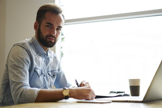 Portrait of young bearded entrepreneur working remote at laptop computer in cafeteria interior.Handsome businessman looking at camera while writing some notes.Copy space area for your advertising