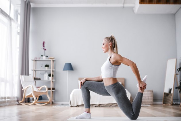 Sporty beautiful woman stretching exercising at home.